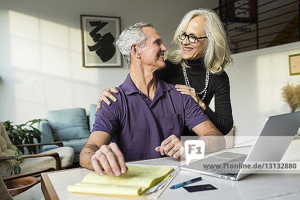 Lächelndes Paar  das sich bei der Benutzung eines Laptops zu Hause von Angesicht zu Angesicht gegenübersteht