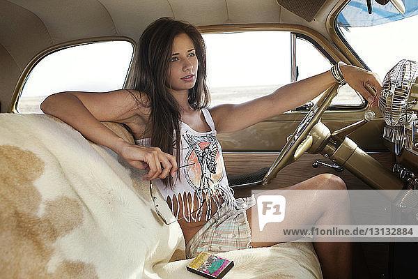 Nachdenkliche junge Frau sitzt in einem Oldtimer