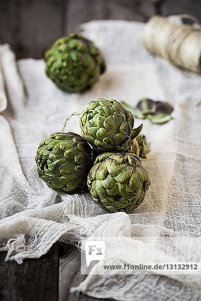 Close-up of artichokes with spool on napkin at table