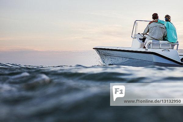 Rückansicht eines Paares  das auf einem Boot auf See gegen den Himmel sitzt