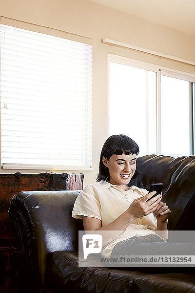 Lächelnde Frau telefoniert  während sie sich zu Hause auf dem Sofa entspannt