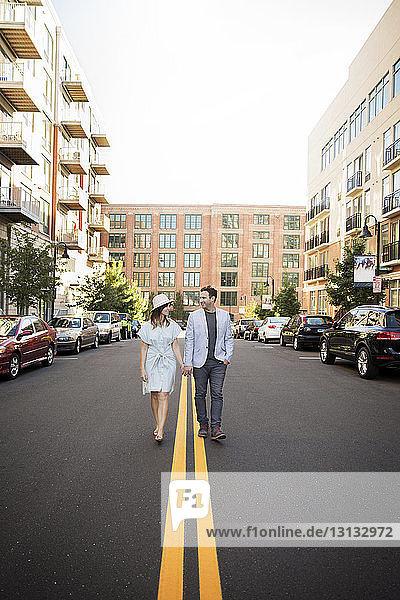 Glückliches Paar geht an einem sonnigen Tag auf der Straße inmitten von Gebäuden