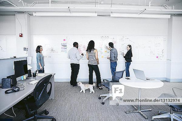 Geschäftsleute schreiben Notizen auf weißer Tafel und diskutieren im Büro