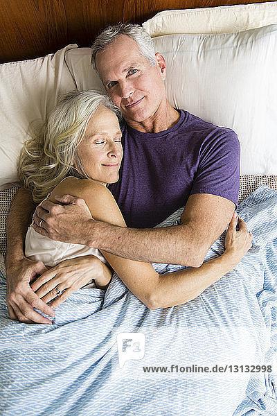 Portrait eines selbstbewussten Mannes  der mit einer schlafenden Frau zu Hause auf dem Bett liegt