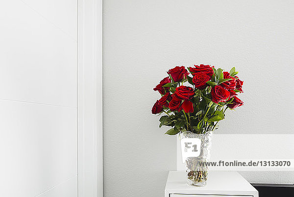 Close-up of roses in vase on table by wall at home