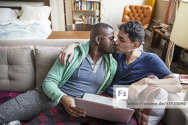 Multi-ethnic homosexual males kissing on sofa at home
