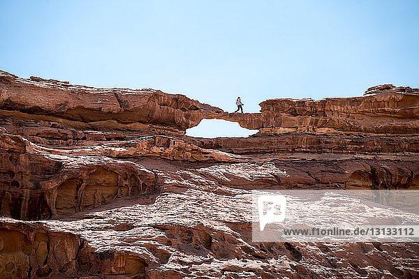 Frau geht auf Felsformation gegen klaren Himmel