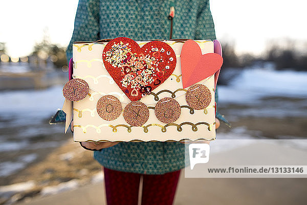 Mittendrin ein Mädchen  das ein Kunstwerk hält  während es im Winter auf dem Feld steht