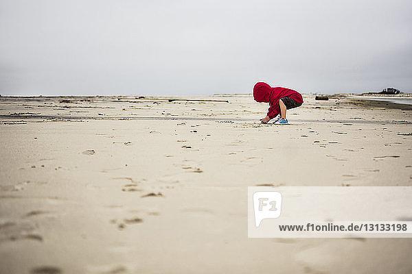Junge spielt mit Sand am Strand gegen klaren Himmel
