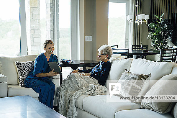 Home caregiver showing tablet computer to senior woman while sitting on sofa in living room
