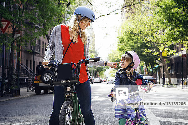 Happy woman touching daughter's nose while standing with Citi Bike on street