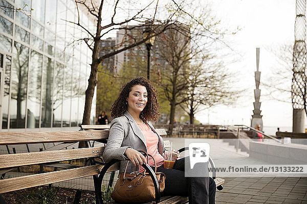 Porträt einer glücklichen Geschäftsfrau  die auf einer Bank am Fussweg sitzt