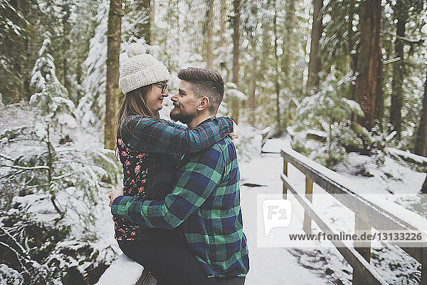 Side view of loving couple looking each other face to face in forest at Lynn Canyon Park during winter