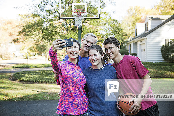 Family taking selfie while standing against basket ball hoop at backyard