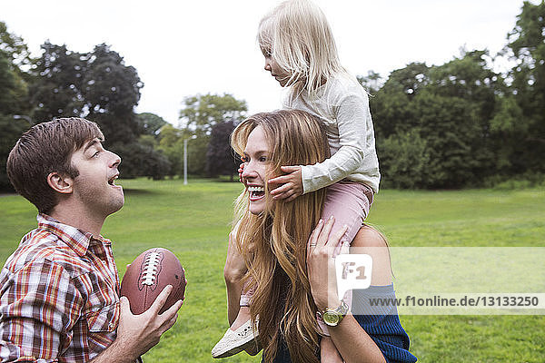 Happy mother carrying daughter on shoulders while looking at man on grassy field