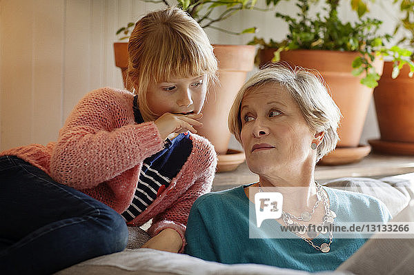 Grandmother looking at granddaughter reading magazine while sitting on sofa