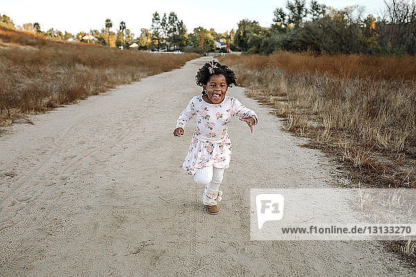 Playful girl running on dirt road in forest