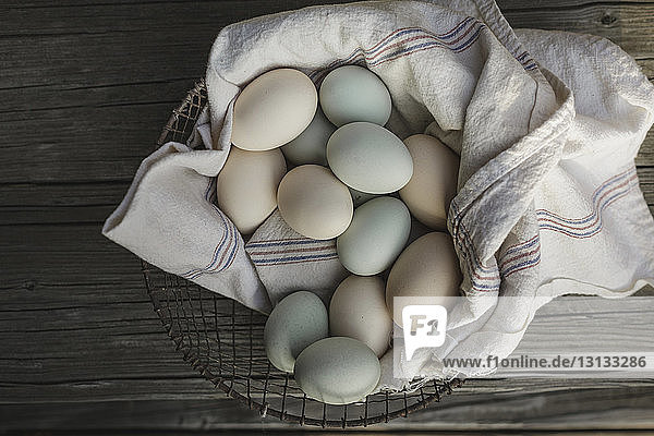 Overhead view of eggs on textile in basket at wooden table