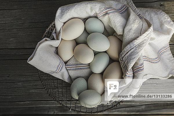Draufsicht von Eiern auf Textil im Korb am Holztisch
