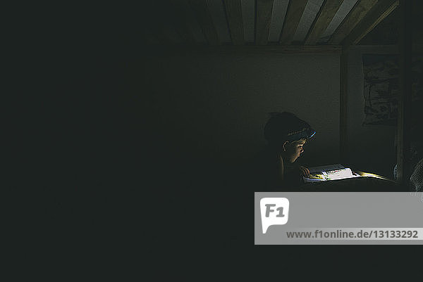 Boy using headlamp while reading book in darkroom
