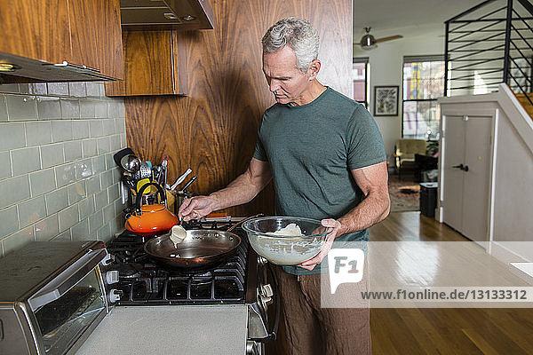 Reifer Mann gießt Teig in die Bratpfanne  während er zu Hause kocht