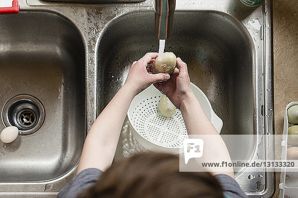 High angle view of boy cleaning egg with water in kitchen