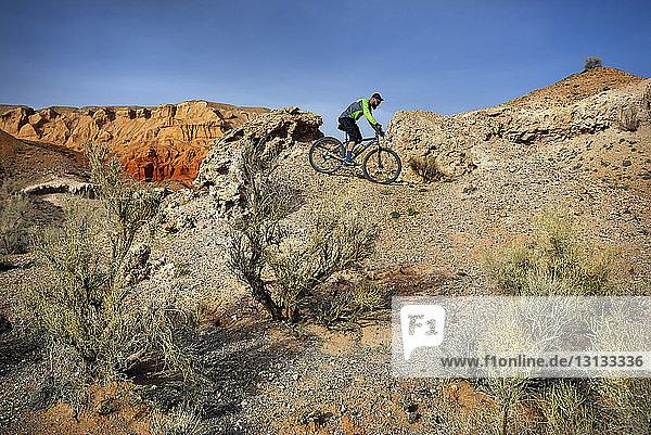 Side view of hiker mountain biking at desert