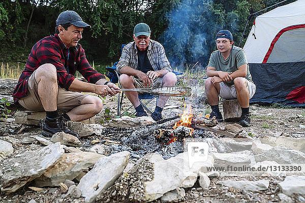 Mittelgroßer Mann kocht Fisch am Lagerfeuer  während er bei Sonnenuntergang mit Freunden auf dem Campingplatz sitzt