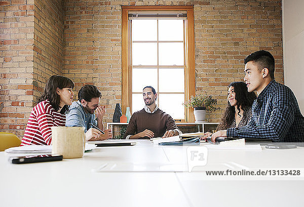 Business people sitting at desk against window during meeting in office
