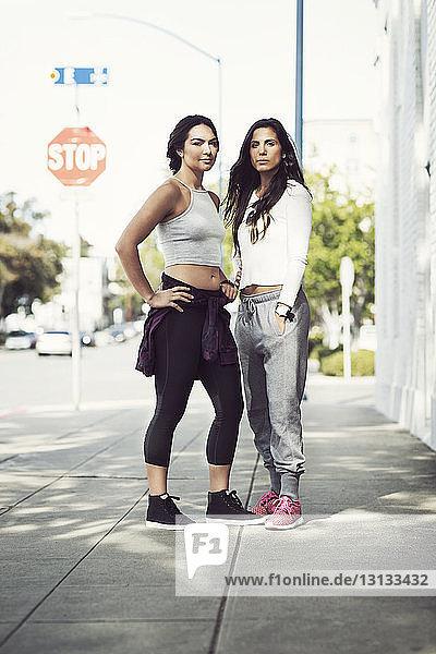 Confident female athletes standing on sidewalk on sunny day