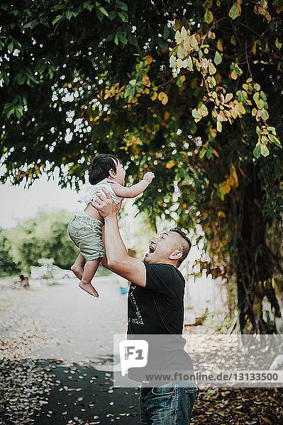Happy father picking up son while standing on street