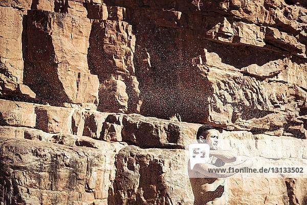 Mann ohne Hemd tanzt an sonnigen Tagen gegen Felsformationen