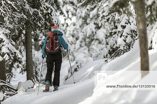 Rückansicht einer Frau mit Himmel  die auf einem schneebedeckten Feld im Wald steht