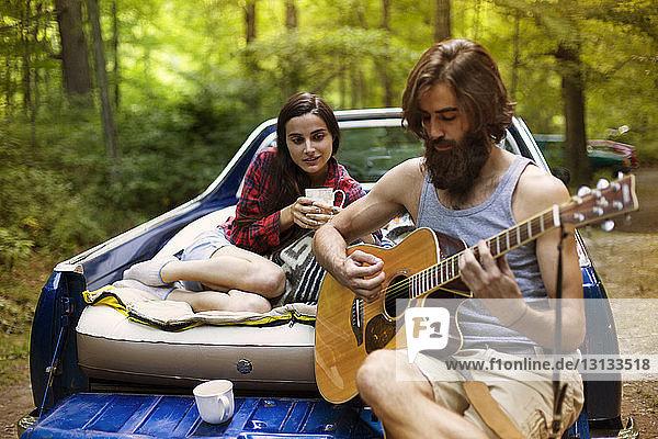 Mann spielt für seine Freundin Gitarre  während er im Pickup im Wald sitzt