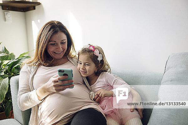 Mutter und Tochter schauen auf ein Smartphone  während sie auf dem Sofa an der Wand sitzen