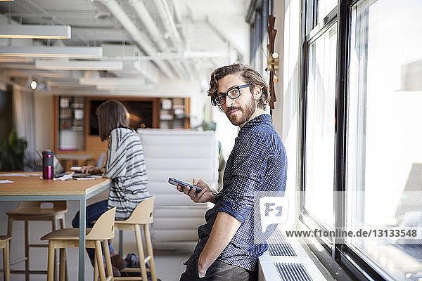 Porträt eines Geschäftsmannes  der ein Mobiltelefon benutzt  während er im Büro am Fenster steht