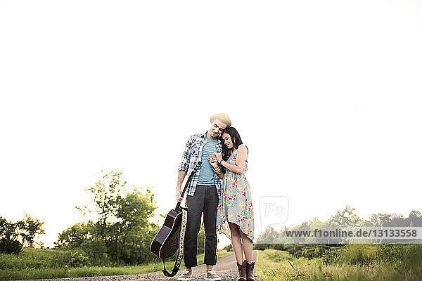 Niedrigwinkelansicht eines lächelnden Paares  das auf der Straße vor klarem Himmel steht