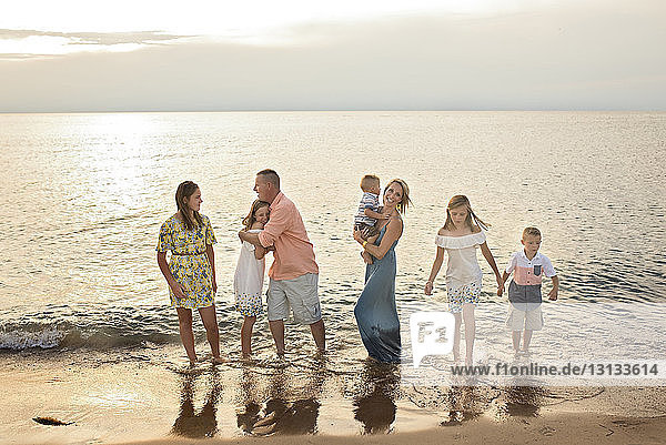 Happy family standing together on shore at beach during sunset