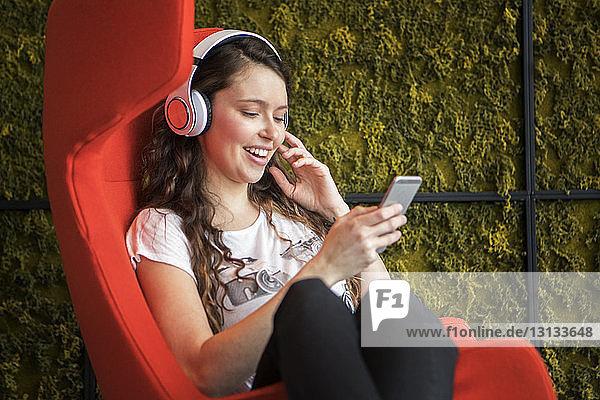 Glückliche Frau  die zu Hause auf einem Sessel sitzend Musik hört