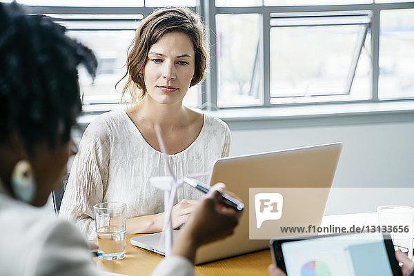 Geschäftsfrau sieht ihren Kollegen an  der im Büro das Modell einer Windkraftanlage erklärt
