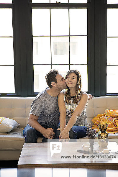 Man kissing happy girlfriend while sitting on sofa at home
