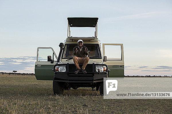 Porträt eines Mannes  der im Serengeti-Nationalpark auf einem Fahrzeug sitzend gegen den Himmel gestikuliert