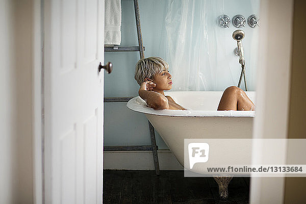 Thoughtful woman relaxing in bathtub at home