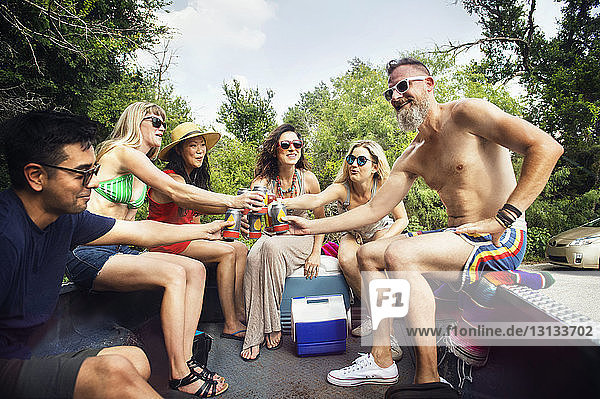 Happy friends toasting drinks while traveling in pick-up truck