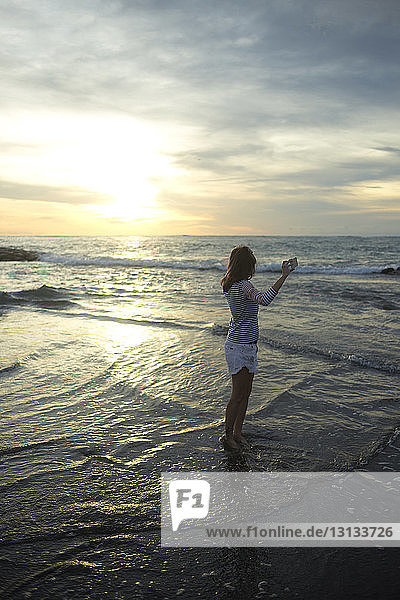 Woman holding mobile phone while standing at beach against cloudy sky during sunset