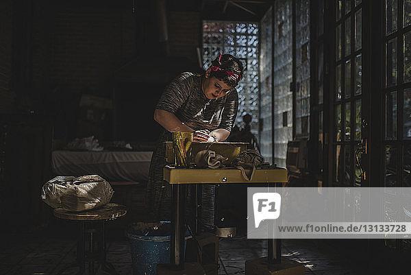 Female craftsperson making clay pot in darkroom
