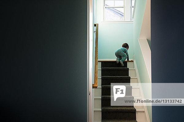 Junge klettert die Stufen durch eine Tür zu Hause hinauf