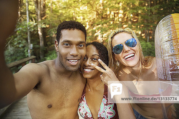 Portrait of cheerful friends in forest