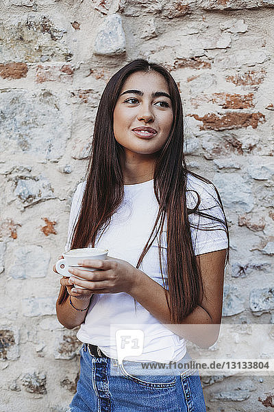 Woman holding cappuccino looking away while standing by old brick wall