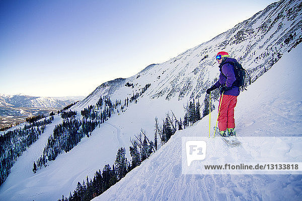 Skier standing on snowy mountain against clear sky